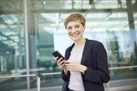 Portrait of blond businesswoman using smartphone - PNEF00685