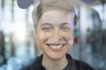 Portrait of blond businesswoman behind glass pane - PNEF00712
