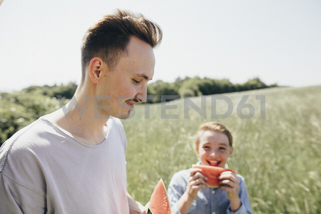 Happy young man and boy on a field eating watermelons - KMKF00289
