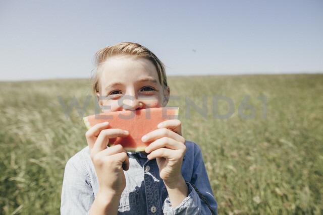 Happy boy on a field holding a watermelon - KMKF00292