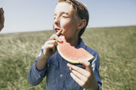 Boy on a field eating a watermelon - KMKF00295