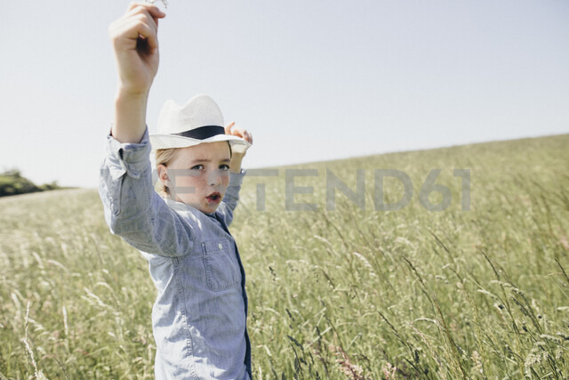 Boy wearing a hat dancing in field - KMKF00298 - Katharina Mikhrin/Westend61