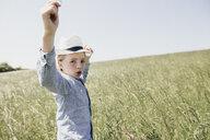 Boy wearing a hat dancing in field - KMKF00298