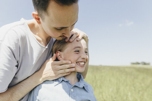 Happy boy and young man in a field - KMKF00304