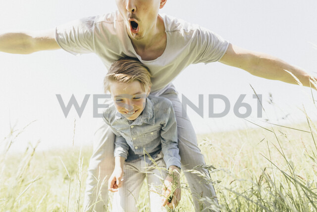 Playful young man and happy boy in a field - KMKF00310