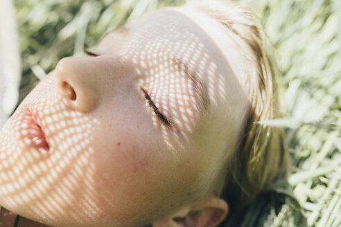 Close-up of boy lying in field - KMKF00313