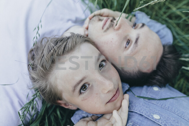 Young man and boy lying in field - KMKF00316