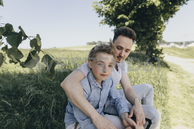 Portrait of young man embracing boy at a field - KMKF00319