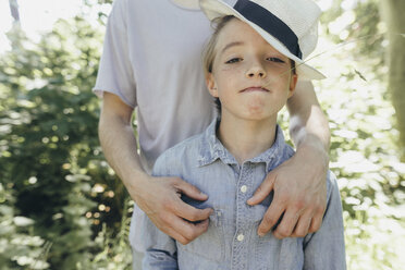 Portrait of boy wearing hat being embraced by a man - KMKF00322