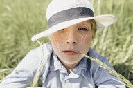 Portrait of boy wearing a hat sitting in field - KMKF00340