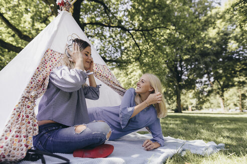 Two happy young women with headphones at a teepee in a park - KMKF00354