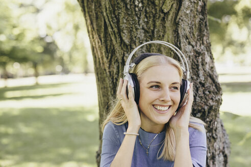 Happy young woman at tree trunk in a park wearing headphones - KMKF00357