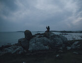 France, Brittany, Landeda, man taking cell phone picture at the coast at dusk - GUSF00944