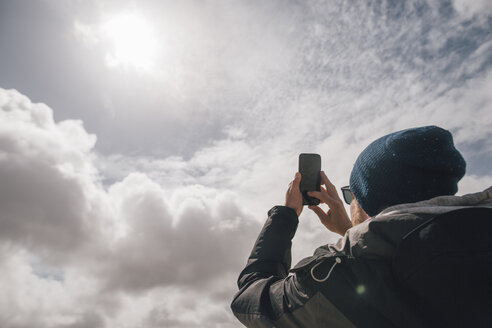 Man holding up cell phone under sunny sky with clouds - GUSF00950