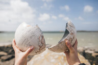 France, Brittany, Landeda, hands holding broken parts of a globe at the coast - GUS00953