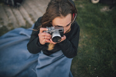 Young woman wrapped in a blanket taking a picture - GUSF00959