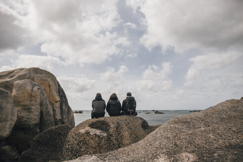 France, Brittany, Meneham, friends sitting on rock formation at the coast - GUSF00962