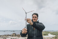 France, Brittany, Meneham, man with miniature wind turbine at the coast - GUSF00971