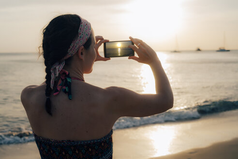 Thailand, Koh Lanta, woman on the beach taking photo with cell phone at sunset - GEMF02053