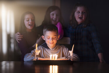Boy surrounded by friends looking at birthday cake smiling - ISF08879