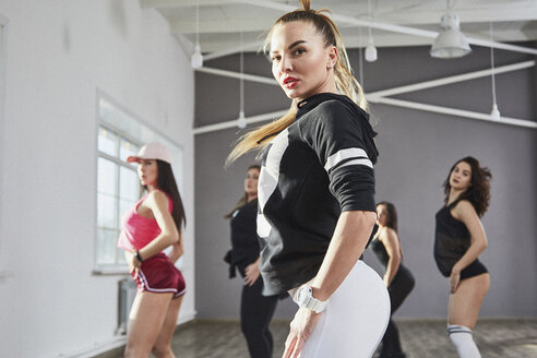 Side view of confident woman dancing with friends in studio - FSIF03034