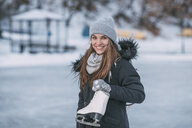 Portrait of smiling young woman standing with ice skate - FSIF03046