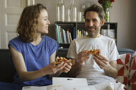 Happy mid adult couple sitting on sofa eating fresh pizza in living room at home - FSIF03061