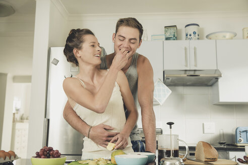Romantic young woman feeding boyfriend whilst preparing breakfast at kitchen counter - ISF08900