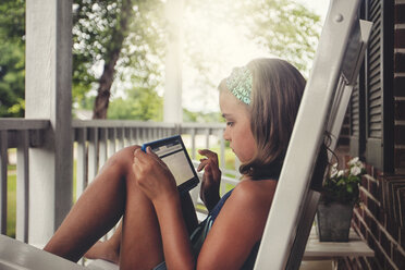 Girls on porch in rocking chair using digital tablet - ISF08933