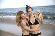 Women hugging and taking selfie with mobile phone on beach, Amagansett, New York, USA - ISF08954