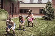 Teenage high school friends leapfrogging outside school - ISF08963
