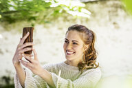 Portrait of relaxed woman taking selfie with cell phone - FMKF05076