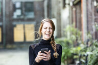 Portrait of laughing woman with smartphone - FMKF05100