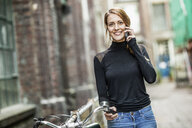 Portrait of smiling woman with bicycle on the phone - FMKF05103