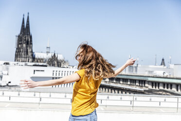Germany, Cologne, woman dancing on roof terrrace - FMKF05106