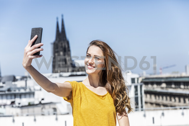 Germany, Cologne, portrait of smiling woman taking selfie with smartphone on roof terrace - FMKF05109 - Jo Kirchherr/Westend61
