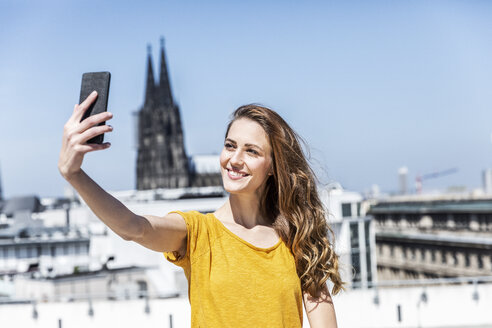 Germany, Cologne, portrait of smiling woman taking selfie with smartphone on roof terrace - FMKF05109