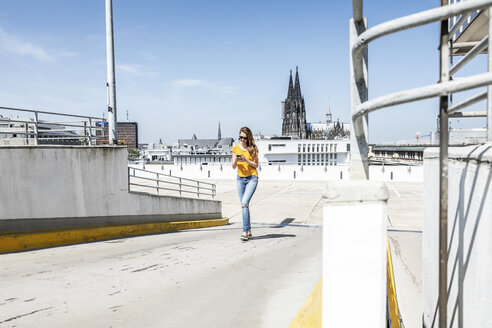 Germany, Cologne, woman walking on ramp of paking level using cell phone - FMKF05115