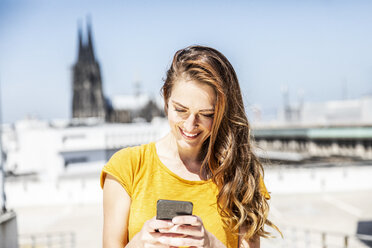 Germany, Cologne, smiling woman using cell phone - FMKF05118