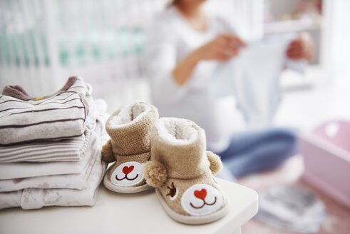 Baby shoes and pregnant woman with baby clothes in baby room - ABIF00532