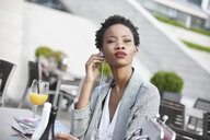 Portrait of businesswoman using  earphones outdoors - ABIF00538