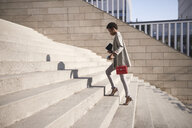 Businesswoman walking up stairs - ABIF00544