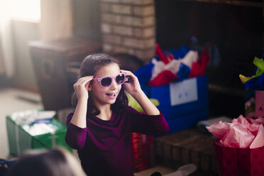 Girl opening presents, trying on sunglasses - ISF09147