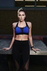 Sportive woman leaning on table tennis table - MMIF00114