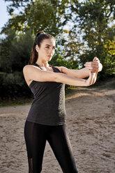 Sportive woman stretching hand - MMIF00120