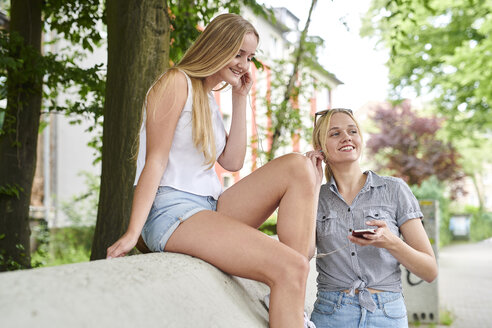 Two young women sharing cell phone and earphones outdoors - MMIF00135
