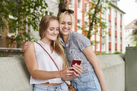 Two happy young women sharing cell phone outdoors - MMIF00138