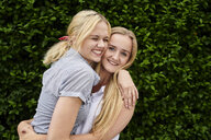 Two happy young women hugging a hedge - MMIF00141