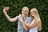 Two happy young women taking a selfie at a hedge - MMIF00144