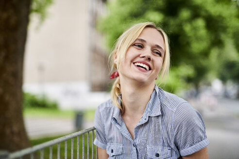 Laughing blond young woman at a fence - MMIF00150